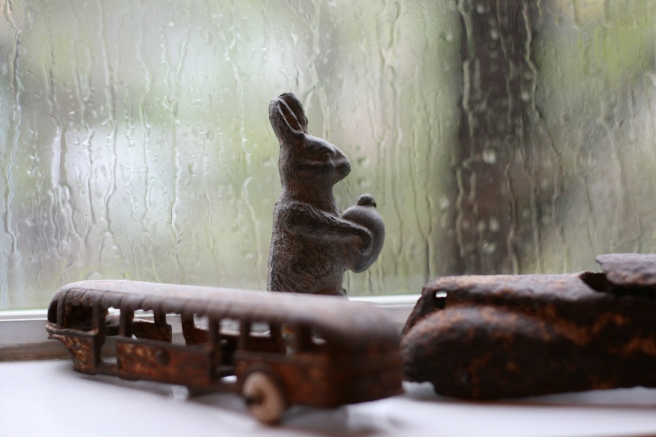 window sill with iron rabbit, train and car