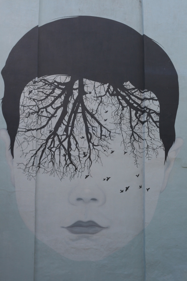 photo of graffiti in NYC of woman's face with tree growing down into her face from her hair